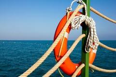 在海和天空蔚蓝的背景的橙色保险索和海绳索 海洋绳索和垂悬在一个绿色岗位o的救生衣 免版税库存照片