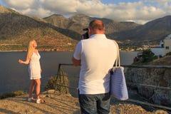 在海和山附近供以人员为他的女朋友照相 库存照片