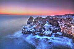 在海和岩石岸的日出 库存图片