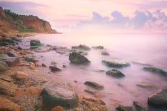 在海和岩石海岸的五颜六色的日落 免版税库存图片