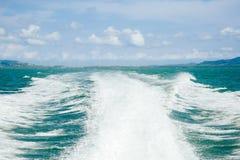 从在海和蓝天白色云彩的速度小船挥动 免版税库存照片