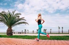 在海堤防的女孩奔跑 活跃生活方式 免版税库存照片