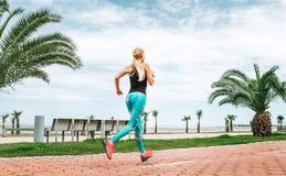 在海堤防的少妇奔跑 活跃生活方式 库存照片
