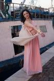 在海塑造在冬天,与长桃红色礼服微笑 免版税图库摄影