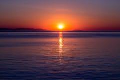 在海天线的日落 明亮的太阳从水表面被反射,平衡天空 免版税库存照片