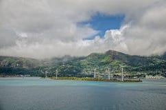 在海岛上的一些台风轮机有青山和大云彩的 库存照片