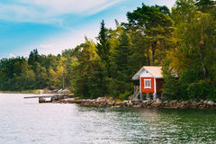 在海岛上的红色小芬兰木蒸汽浴原木小屋在秋天海 免版税库存照片