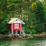 在海岛上的红色芬兰木巴恩蒸汽浴原木小屋在夏天 免版税库存图片