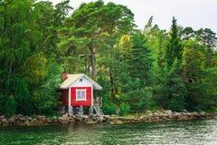 在海岛上的红色芬兰木巴恩蒸汽浴原木小屋在夏天 库存图片