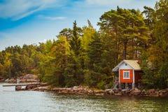 在海岛上的红色芬兰木巴恩蒸汽浴原木小屋在秋天 图库摄影
