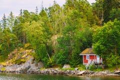 在海岛上的红色芬兰木巴恩蒸汽浴原木小屋 免版税库存照片