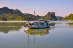 在海岛中的通勤者船在下龙湾 免版税库存图片