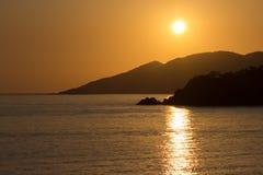 在海岛和风平浪静的黄色红色日落 库存图片