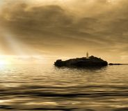 在海岛灯塔的日落 免版税库存图片