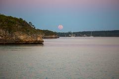 在海岛解决的桃红色月出 免版税库存照片
