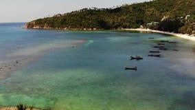 在海岛附近岸的小船  漂浮在镇静大海的传统五颜六色的渔船在白色沙子海岸附近  股票录像