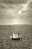 在海岛附近的古色古香的船 免版税库存图片