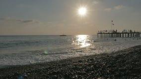 在海岸人民的一个木码头游泳,享用波浪 风雨如磐的海和美好的日落 影视素材