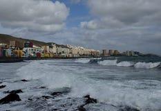 在海岸和城市的强的波浪 免版税库存照片