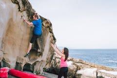 在海岸帮助的eachother的年轻夫妇攀岩峭壁 免版税库存图片