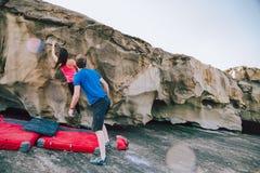 在海岸帮助的eachother的年轻夫妇攀岩峭壁 库存图片