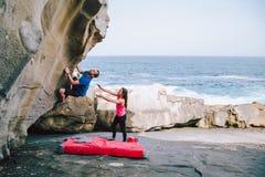 在海岸帮助的eachother的年轻夫妇攀岩峭壁 免版税库存照片