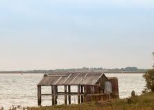在海岸水海边缘的被放弃的棚子棚子  免版税库存照片