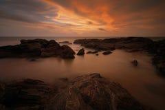 在海岸海的日落有太阳的 与太阳的岩石海岸在日落期间 在本托特,斯里兰卡,亚洲的日落 美好的风景与 免版税库存照片