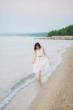 去在海岸的一个愉快的微笑的女孩 库存照片