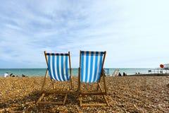 在海岸的两张空的镶边折叠的海滩睡椅在布赖顿,未知的人民 图库摄影