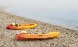 在海岸的五颜六色的独木舟小船在大雾 库存图片