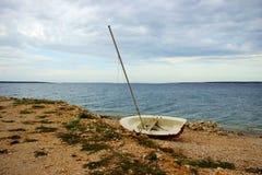 在海岸的偏僻的老小船 免版税库存图片