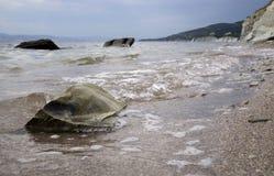 在海岸的大石头 湿沙子,透明水 阴暗多云天空 库存照片