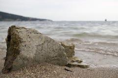 在海岸的大石头 湿沙子,透明水 阴暗多云天空 库存图片
