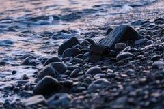 在海岸的小卵石在日落 图库摄影