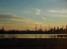 在海岸的工业风景与管子塔和精炼厂 免版税库存图片