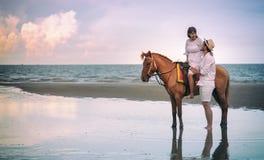在海岸的幼小夫妇骑乘马 库存照片
