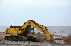在海岸的挖掘机 免版税库存图片