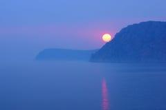 在海岸的日落在与大太阳的雾 库存图片