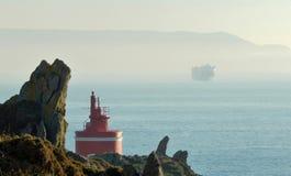 在海岸的灯塔与货轮在加利西亚,西班牙,欧洲 免版税库存照片