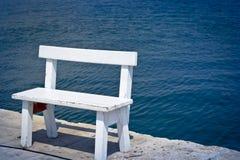 在海岸的白色长凳 库存照片