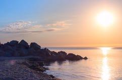 在海岸的石海滩 蓝色展望期天空 日出的反射 免版税库存图片