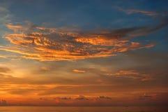 在海岸的美好的日落与一朵大发光的云彩 图库摄影