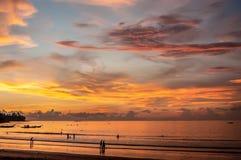 在海岸的美好的日落与与一朵光亮云彩的光 走在海滩的人剪影  免版税库存照片