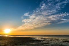 在海岸的美好的日落与到达天际的云彩 免版税库存照片