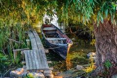 在海岸的老小船在码头附近 与木船坞的土气风景在夏天晚上 免版税库存图片