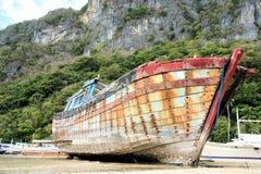 在海岸的老打破的小船 库存图片