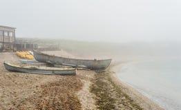 在海岸的老渔船在大雾 免版税库存图片