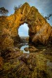 在海岸的自然曲拱在金黄小时 免版税库存图片