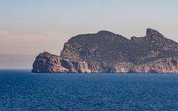 在海岸的陡峭的小山与在上面的小灯塔 免版税库存图片